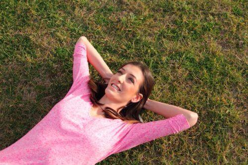 芝生に寝っころがる女性